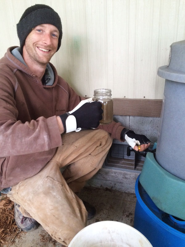 Pete holding compost tea from the brewer