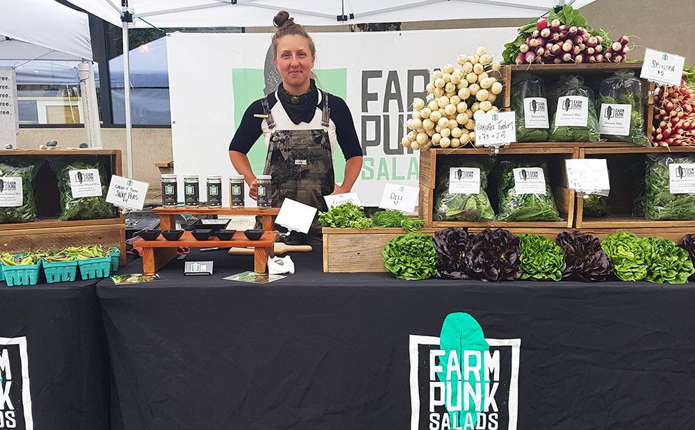 Quinn at the Farm Punk Salads booth at a farmers market