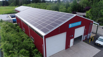 aerial angled view of two structures at Headwaters Farm, including a barn in the foreground and a storage shed in the background, with solar-panel-covered roofs visible on both structures