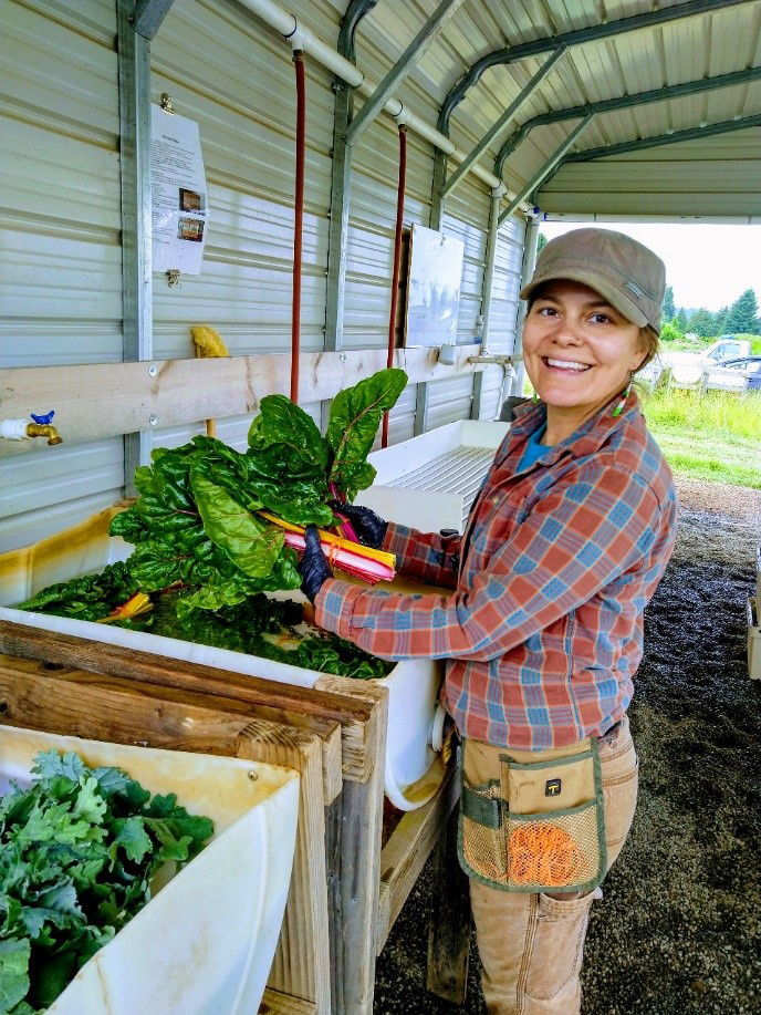 Reiden, a farmer enrolled in the Headwaters Farm Incubator program, washes vegetables while turning toward the camera and smiling. In the background a wall and roof overhang is visible, and the farm past that